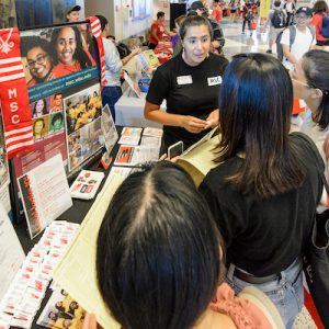 Students check out the Multicultural Student Center booth during the Fall Student Organization Fair at the Kohl Center at the University of Wisconsin-Madison on Sept. 12, 2018. The two-day fair is an opportunity for students to learn about special-interest groups, activities and services offered by more than 400 represented student organizations on campus. (Photo by Bryce Richter / UW-Madison)