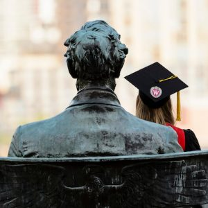 A soon-to-be graduate sits on the Abraham Lincoln statue wearing her cap and gown attire.