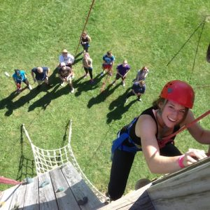 A female student is featured climbing a ropes course wall smiling at the camera.