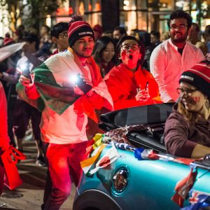 Thousands of spectators cheer as spirited students dance and parade floats -- including this one hosted by International Student Services (ISS) -- travel down State Street during the University of Wisconsin-Madison's Homecoming Parade on Oct. 19, 2018. The annual parade is one of many Homecoming week activities sponsored by the Wisconsin Alumni Association (WAA). (Photo by Lauren Justice / UW-Madison)